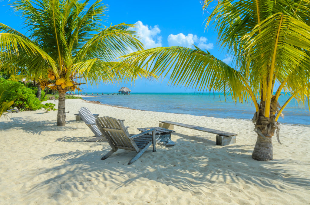 Lounge chairs on a sandy beach in Placencia, Belize